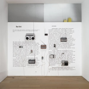 Art Review, 2013, 12 radios, cables, amplifier over photo mural Variable dimensions