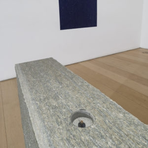 """Oltremare Verso Sud"", 1967-2018, Yellow Lucerne granite, magnetic needle, glass, acrylic paint on wall Variable dimensions (Stone 70 x 80 x 16 cm Oltremare 70 x 80 cm)"